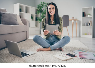 Full length portrait of pretty positive person sit on floor hands hold tablet look camera toothy smile home indoors