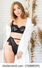 Full length portrait of pretty woman wearing black lingerie standing