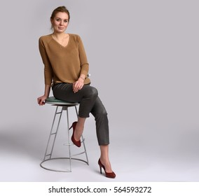 full length portrait of pretty woman sits on a chair. Studio shot