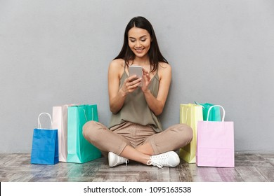 Full length portrait of a pretty young asian woman sitting on a floor with shopping bags and using mobile phone over gray background