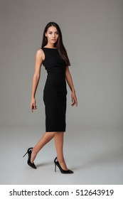 Full length portrait of a pretty young woman wearing black dress and high heels isolated on a gray background