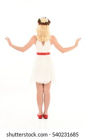 Full length portrait of a pretty young model wearing a white dress and festive flower crown. standing pose, isolated against a white studio background.