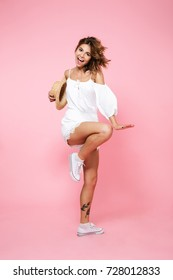 Full length portrait of pretty young girl in summer clothes dancing and having fun isolated over pink background