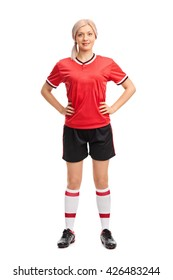 Full length portrait of a professional female soccer player in a red jersey isolated on white background
