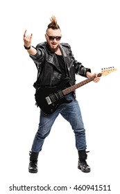 Full length portrait of a punk holding an electric guitar and making a rock hand gesture isolated on white background