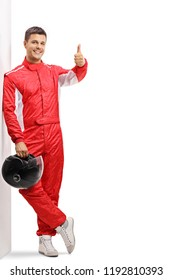 Full length portrait of a racer leaning against a wall and holding his thumb up isolated on white background