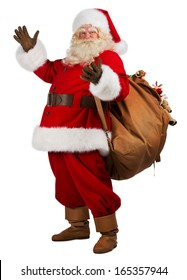 Full length portrait of Real Santa Claus carrying big bag full of gifts, isolated on white background