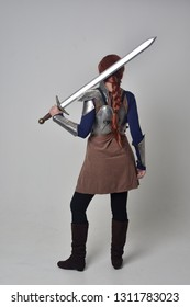 full length portrait of a  red haired girl wearing medieval warrior costume and steel armour, standing pose on grey studio background.