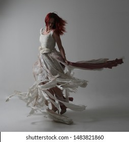 full length portrait of red haired girl wearing torn and tattered wedding dress. Standing pose against a studio background with contrasty shadow lighting.