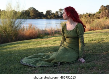 full length portrait of a red haired beautiful lady wearing a green medieval gown near a lake.