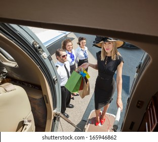 Full length portrait of rich woman with shopping bags boarding private jet while pilot and airhostess looking at her