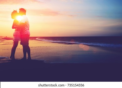 Full length portrait of romantic couple in love kissing on the beach during sunset. Honeymoon and vacation holidays