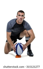 Full length portrait of rugby player in black jersey placing ball against white background