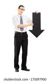 Full length portrait of sad man holding a big black arrow pointing down isolated on white background