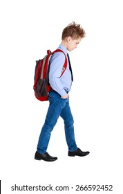 Full length portrait of a sad school boy walking, isolated on white background