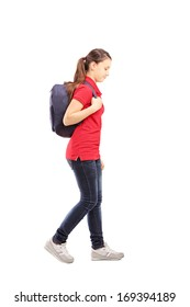 Full length portrait of a sad schoolgirl with a bag walking, isolated on white background