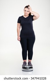 Full length portrait of a sad thick woman standing on weighing machine isolated on a white background