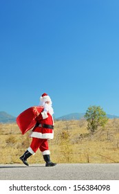 Full length portrait of a santa claus with bag walking on an open road