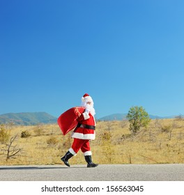 Full length portrait of a santa claus with bag walking on an open road, shot with a tilt and shift lens