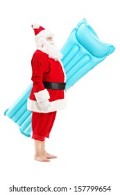 Full length portrait of a Santa claus holding a swimming mattress on vacation, isolated on white background