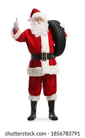 Full length portrait of santa claus holding a car tire and showing thumbs up isolated on white background