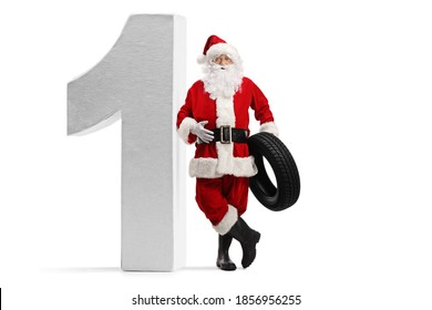 Full length portrait of santa claus leaning on a big number on and holding a car tire isolated on white background