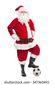 Full length portrait of Santa Claus stepping over a football and looking at the camera isolated on white background