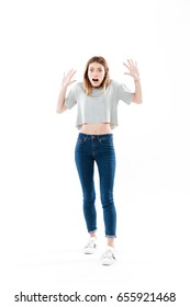 Full length portrait of a scared frightened girl standing and screaming isolated over white background