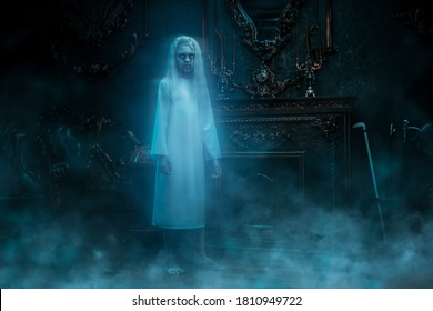 A full length portrait of a scary pale girl from a horror film in vintage room. Zombie, halloween.