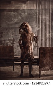 A full length portrait of a scary zombie girl standing near a bed. Halloween. Horror film.