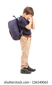 Full length portrait of a schoolboy crying, isolated on white background