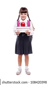 Full length portrait of a schoolgirl in uniform standing on white background and holding books and apple