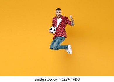 Full length portrait screaming man football fan in red shirt cheer up support favorite team with soccer ball jumping doing winner gesture isolated on yellow background. People sport leisure concept