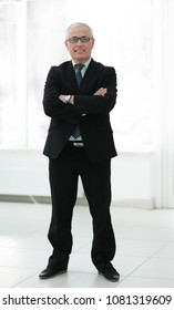 Full length portrait of senior businessman standing against white background with arms crossed.