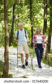 Full length portrait of senior couple nordic walking on the forest.