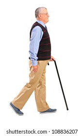 Full length portrait of a senior man walking with cane isolated on white background