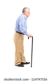 Full length portrait of a senior man walking with a cane isolated on white background