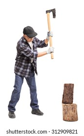 Full length portrait of a senior man splitting wood with a hand axe isolated on white background