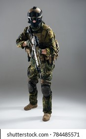 Full length portrait of serious man keeping assault rifle in hand. Army concept