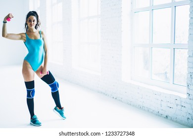 Full length portrait of sexy fitness girl lifting dumbbells doing exercises for arms muscles,sportswoman looking at camera training upper body on workout looking at camera in white interior gym
