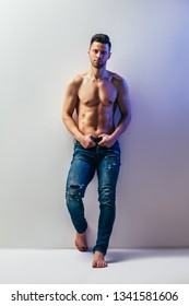 Full length portrait of sexy muscular shirtless man posing in studio. Male beauty