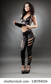 Full length portrait of a sexy woman posing in leather suit