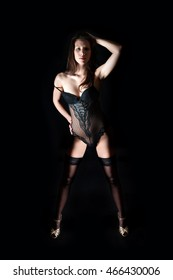 Full length portrait of a sexy woman wearing black lingerie and golden high heels in front of dark studio background