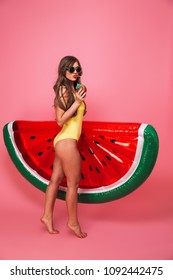 Full length portrait of a sexy young woman dressed in swimsuit posing while standing with inflatable watermelon and drinking cocktail isolated over pink background