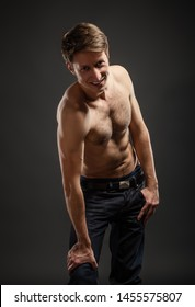 Full length portrait of a sexy young man in jeans and shirtless posing at studio.