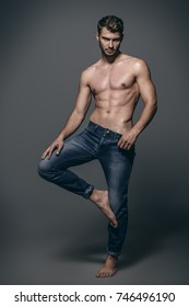Full length portrait of a sexy young man in jeans and shirtless posing at studio. Gray background. Men's health. Beauty, jeans fashion.