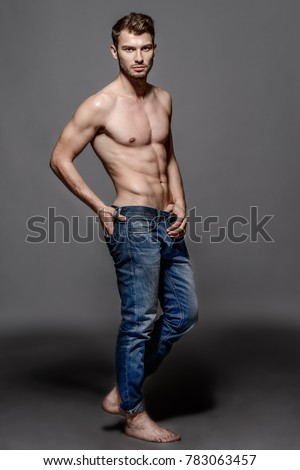 67835da901 Full length portrait of a sexy young man in jeans and shirtless posing at  studio.