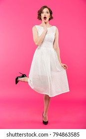 Full length portrait of a shocked girl dressed in dress posing while standing isolated over pink background