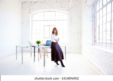 Full length portrait shot of elegant middle aged businesswoman with toothy smile standing at the desk in the office and looking at camera.