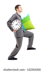 Full length portrait of a sleepwalker with a pillow and a clock isolated on white background
